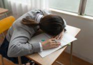 机で寝る学生